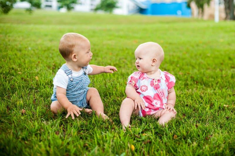 Το ευτυχές αγοράκι δύο και μια ηλικία κοριτσιών 9 μηνών, καθμένος στη χλόη και αλληλεπιδρούν, μιλούν, εξετάζουν το ένα το άλλο στοκ φωτογραφία