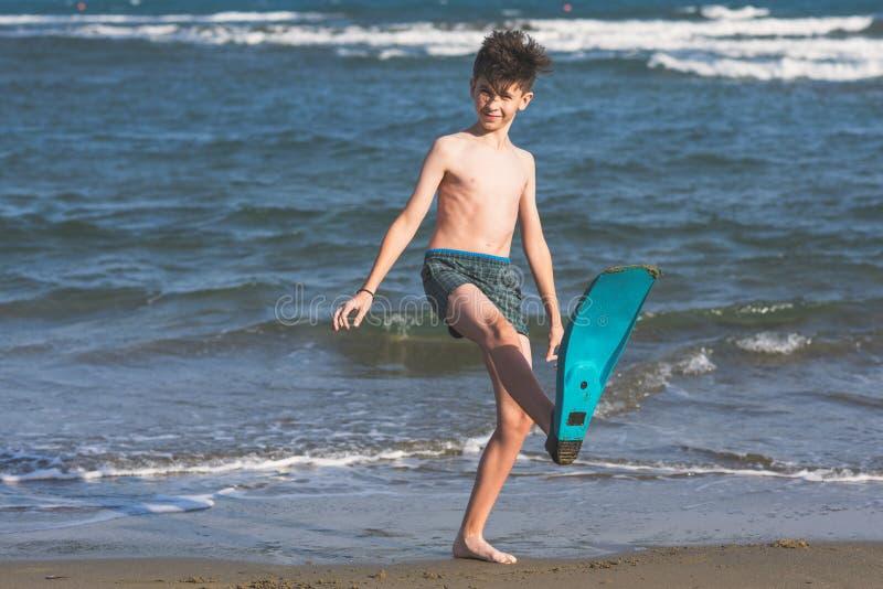 Το ευτυχές αγόρι εφήβων κολυμπά τα βατραχοπέδιλα που έχουν τη διασκέδαση στην άμμο Ð ¾ ν η παραλία στοκ εικόνες