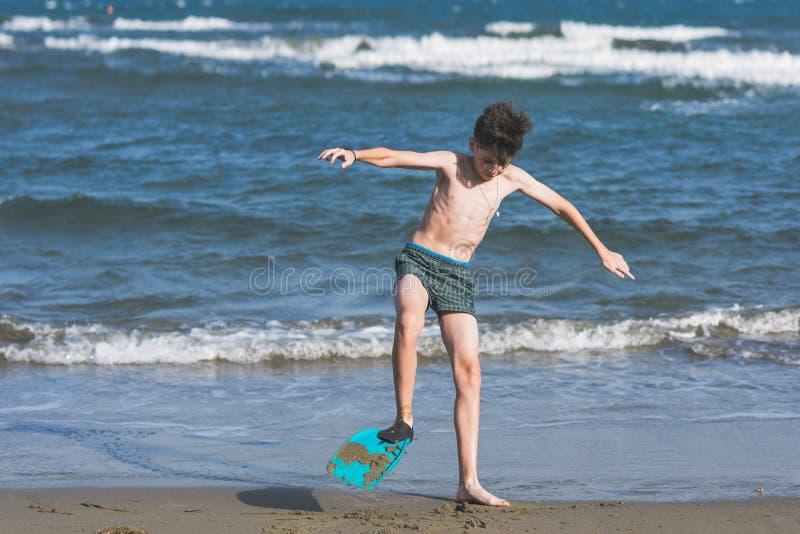 Το ευτυχές αγόρι εφήβων κολυμπά τα βατραχοπέδιλα που έχουν τη διασκέδαση στην άμμο Ð ¾ ν η παραλία στοκ φωτογραφίες