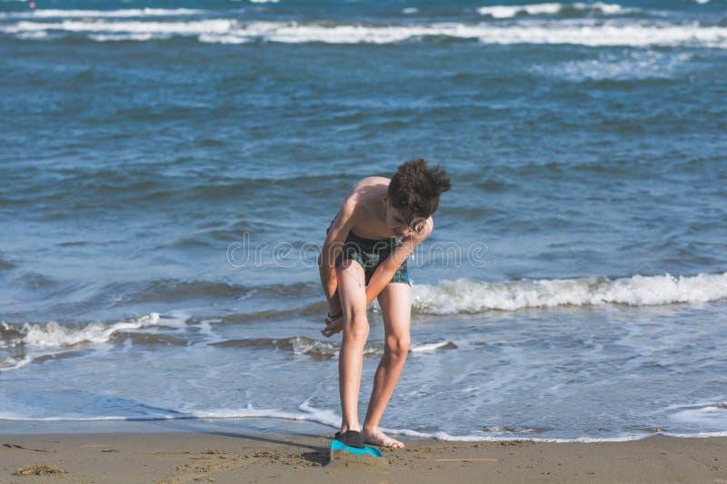 Το ευτυχές αγόρι εφήβων κολυμπά τα βατραχοπέδιλα που έχουν τη διασκέδαση στην άμμο Ð ¾ ν η παραλία κατά τη διάρκεια των θερινών δ στοκ εικόνες