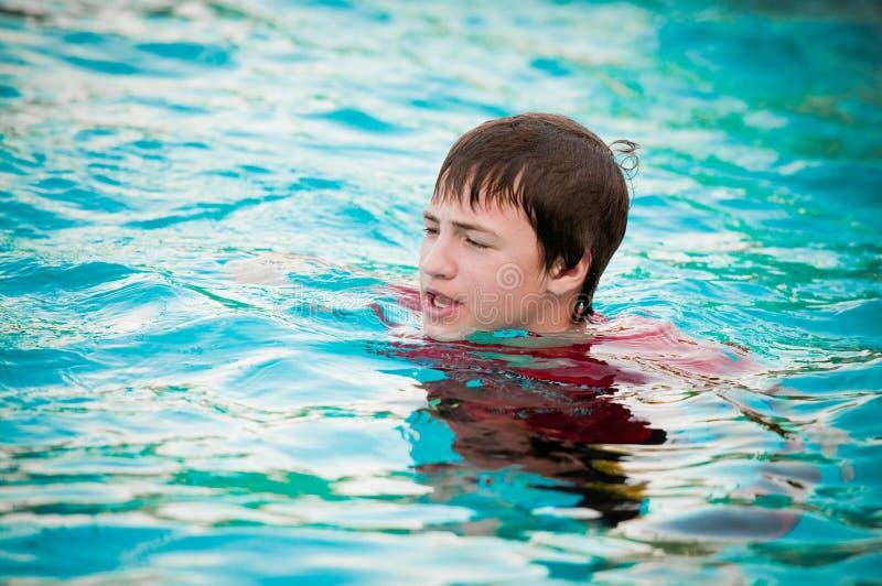 Το ευτυχές αγόρι εφήβων στην πισίνα με τα χείλια στοκ εικόνα
