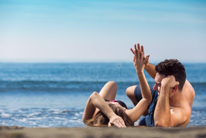 Το ευτυχές ακριβώς παντρεμένο ζευγάρι βάζει στην παραλία στοκ εικόνα με δικαίωμα ελεύθερης χρήσης