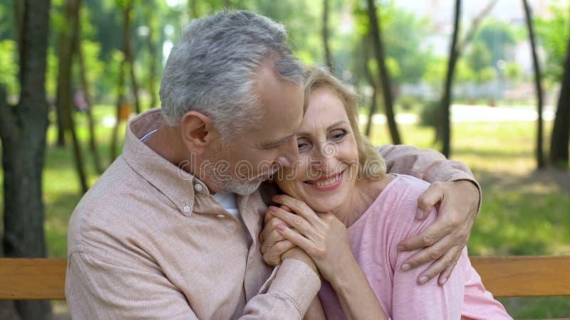 Το ευτυχές ανώτερο ζεύγος αγκαλιάζει στο πάρκο, άνδρας που αγκαλιάζει τη γυναίκα, αγάπη μέχρι τη μεγάλη ηλικία στοκ εικόνες