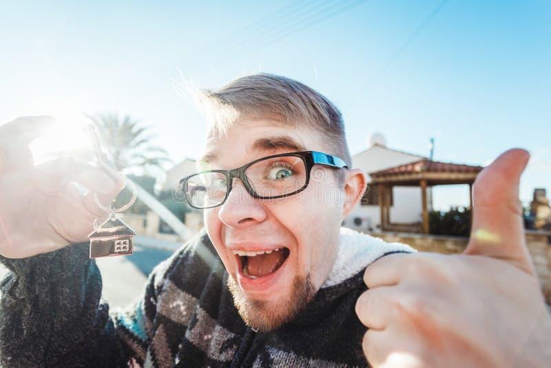 Το ευτυχές αστείο άτομο κρατά τα κλειδιά σπιτιών στο σπίτι που διαμορφώνεται keychain μπροστά από ένα νέο σπίτι στοκ εικόνες