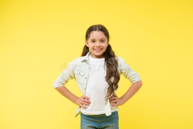 Το ευτυχές βέβαιο παιδί κρατά τα χέρια στα ισχία Εύθυμος και βέβαιος Χαριτωμένο χαμόγελο μικρών κοριτσιών Περιστασιακός κοιτάξτε  στοκ εικόνες με δικαίωμα ελεύθερης χρήσης