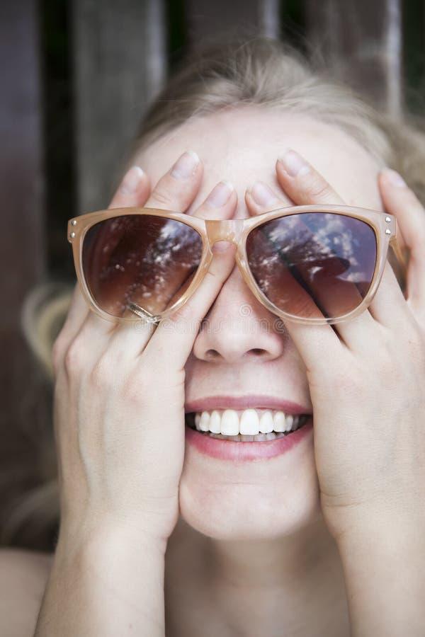 Το ευτυχές, γελώντας κορίτσι κάλυψε το πρόσωπό της με το χέρι, που φορούν sunglass στοκ εικόνα