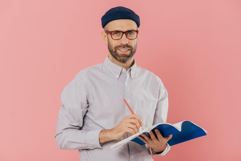 Το ευτυχές ελκυστικό άτομο με τις καλαμιές, φορά τα διαφανή γυαλιά, μοντέρνο καπέλο και το πουκάμισο, γράφει με τη μάνδρα στο σημ στοκ εικόνες