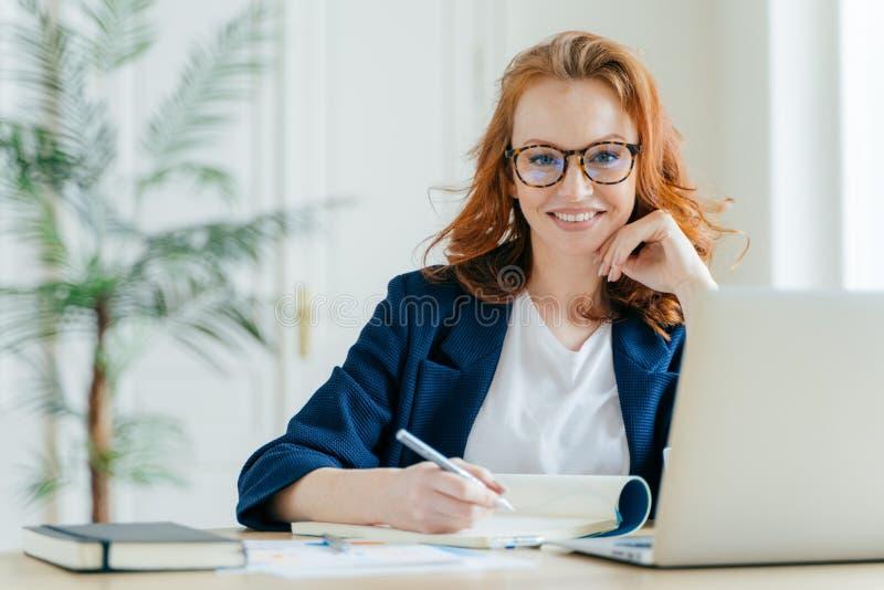 Το ευτυχές επιτυχές θηλυκό γράφει τον πίνακα ελέγχου στο σημειωματάριο, εργάζεται στις δημιουργικές ιδέες για το πρόγραμμα ξεκινή στοκ φωτογραφίες με δικαίωμα ελεύθερης χρήσης