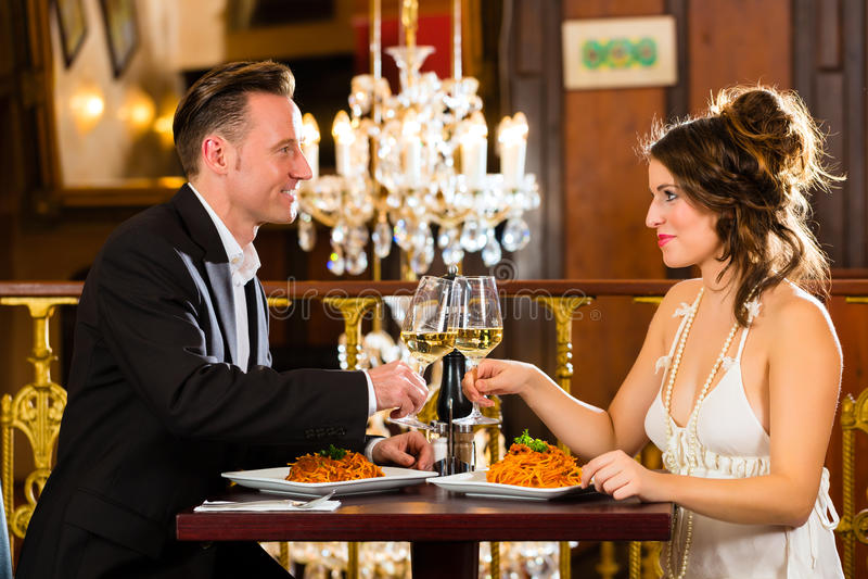 Το ευτυχές ζεύγος έχει μια ρομαντική ημερομηνία στο εστιατόριο στοκ φωτογραφία