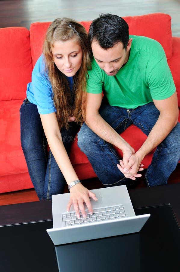 Το ευτυχές ζεύγος έχει τη διασκέδαση και την εργασία για το lap-top στο σπίτι στοκ φωτογραφία με δικαίωμα ελεύθερης χρήσης
