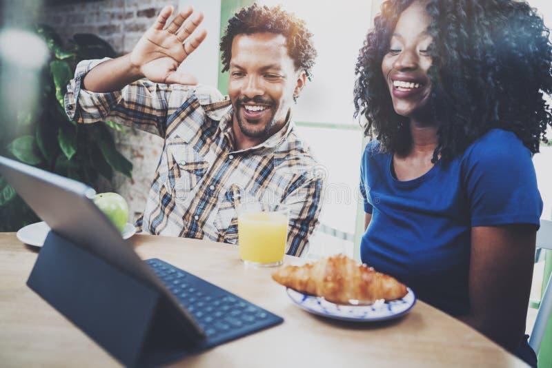 Το ευτυχές ζεύγος αφροαμερικάνων έχει την τηλεοπτική συνομιλία μαζί μέσω της ταμπλέτας αφής το πρωί στον ξύλινο πίνακα στοκ εικόνες
