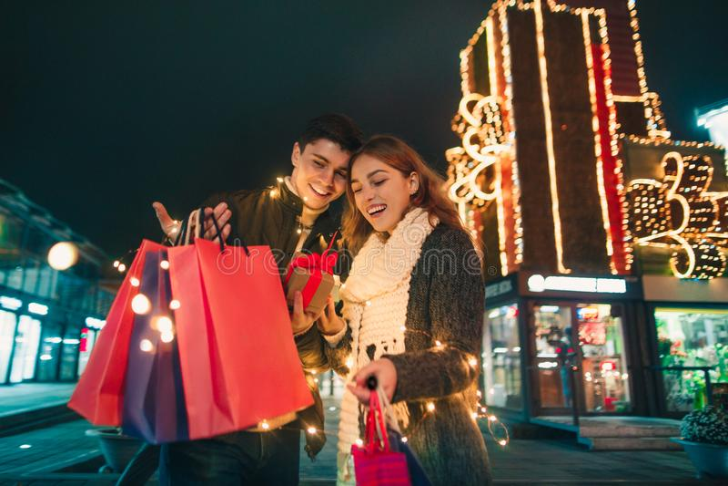 Το ευτυχές ζεύγος με τις αγορές τοποθετεί την απόλαυση της νύχτας στο υπόβαθρο πόλεων σε σάκκο στοκ φωτογραφία με δικαίωμα ελεύθερης χρήσης