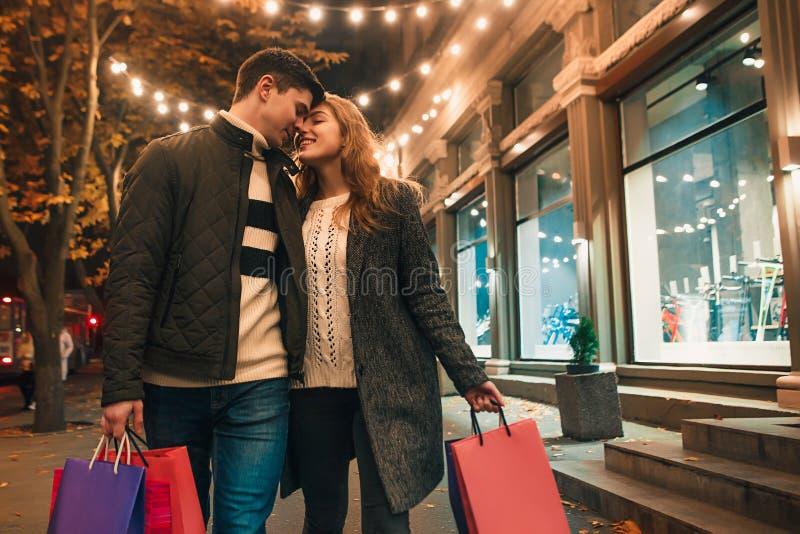 Το ευτυχές ζεύγος με τις αγορές τοποθετεί την απόλαυση της νύχτας στο υπόβαθρο πόλεων σε σάκκο στοκ εικόνες
