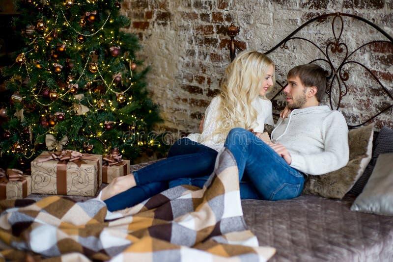 Το ευτυχές ζεύγος των εραστών στα άσπρα πουλόβερ δίνει σε μεταξύ τους τα δώρα στοκ φωτογραφία