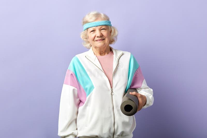 Το ευτυχές θηλυκό χαλί γιόγκας εκμετάλλευσης συνταξιούχων στα χέρια, έρχεται στην κατηγορία γιόγκας στο στούντιο στοκ φωτογραφία