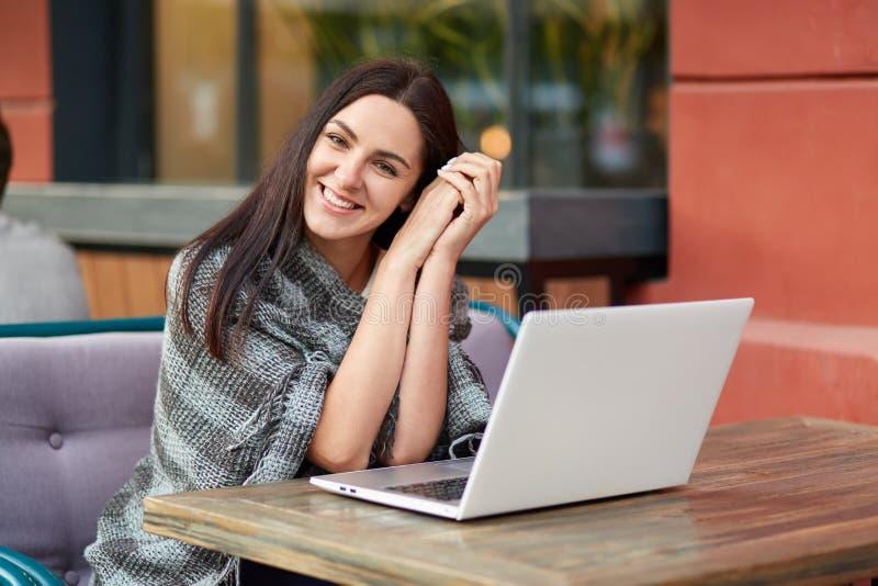Το ευτυχές θηλυκό freelancer που ικανοποιεί με την εργασία απόστασης, εργασίες στο υπαίθριο εστιατόριο, έχει το coverlet στους ώμ στοκ φωτογραφίες με δικαίωμα ελεύθερης χρήσης