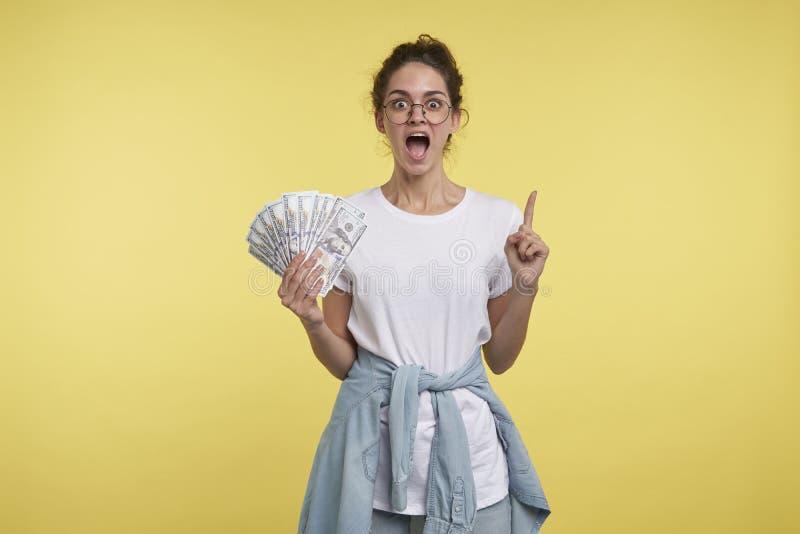 Το ευτυχές και κραυγάζοντας θετικά θηλυκό με μέρη των χρημάτων το χέρι, παρουσιάζει δάχτυλο μέχρι το διάστημα αντιγράφων στοκ εικόνα