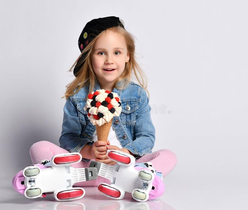 Το ευτυχές και συγκινημένο παιδί κοριτσάκι στον ειδικό κύλινδρο κάνει πατινάζ rollerblades πηγαίνοντας να φάει ένα μεγάλο παγωτό  στοκ φωτογραφίες