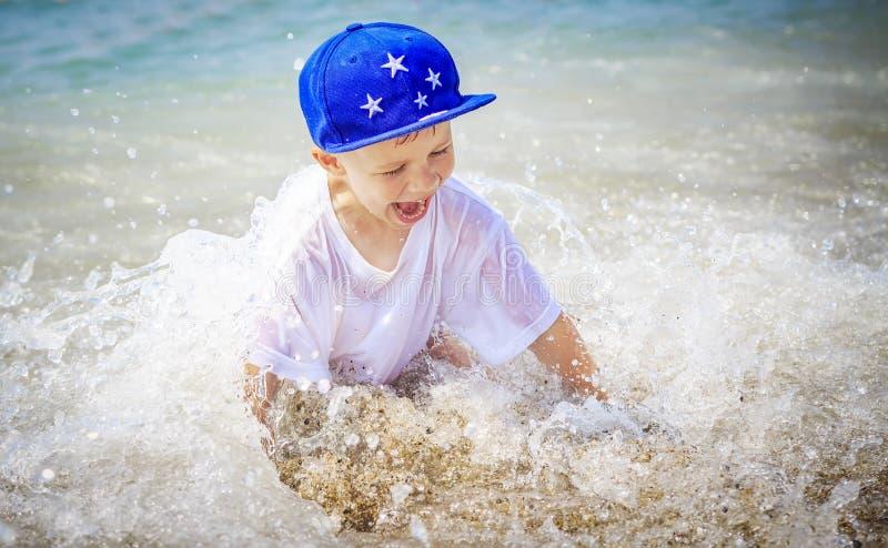 Το ευτυχές καυκάσιο αγόρι λούζει στη θάλασσα στις θερινές διακοπές Χαμογελώντας παιδί στο θαλάσσιο νερό στοκ εικόνα