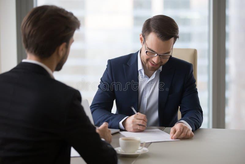 Το ευτυχές κλείσιμο επιχειρησιακών συμβάσεων σημαδιών CEO εξετάζει το συνεργάτη στοκ φωτογραφίες