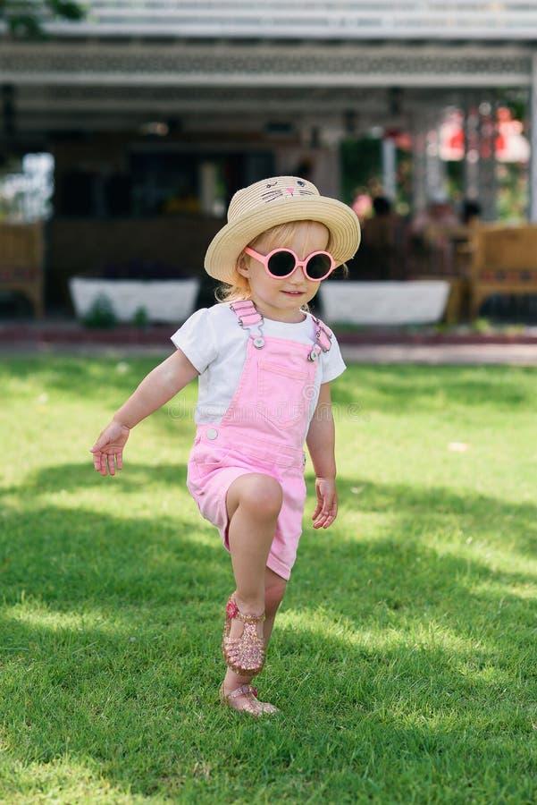 Το ευτυχές κορίτσι έντυσε στα μοντέρνα περιστασιακά φωτεινά ενδύματα και τα ρόδινα γυαλιά ηλίου που έχουν τη διασκέδαση στον πράσ στοκ εικόνες