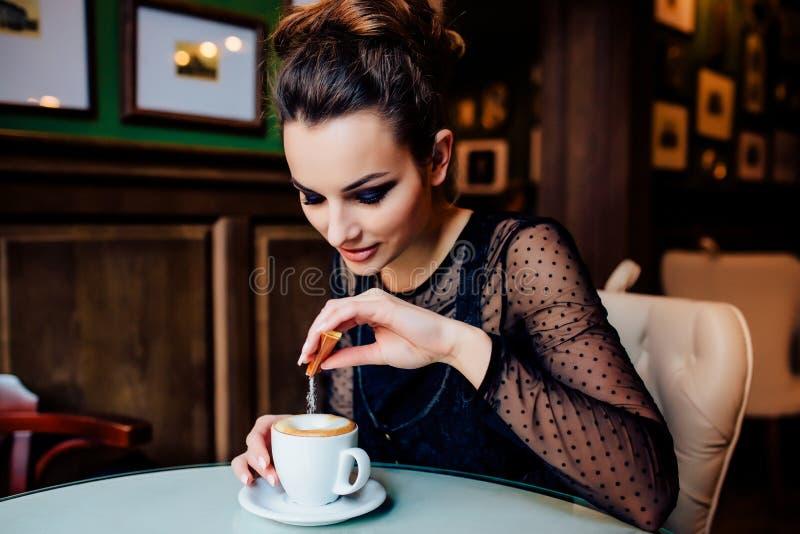 Το ευτυχές κορίτσι έχει το φλιτζάνι του καφέ στο εσωτερικό στοκ φωτογραφία με δικαίωμα ελεύθερης χρήσης