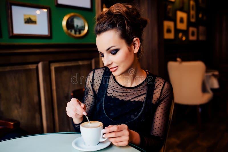 Το ευτυχές κορίτσι έχει το φλιτζάνι του καφέ στο εσωτερικό στοκ εικόνες με δικαίωμα ελεύθερης χρήσης