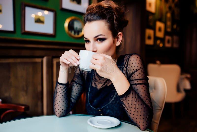 Το ευτυχές κορίτσι έχει το φλιτζάνι του καφέ στο εσωτερικό στοκ εικόνα με δικαίωμα ελεύθερης χρήσης