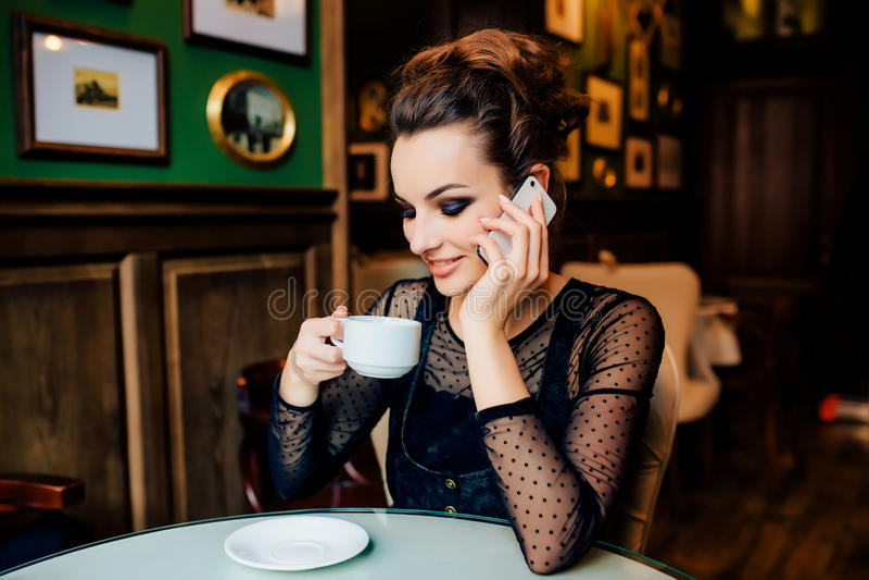Το ευτυχές κορίτσι έχει το φλυτζάνι του πράσινου τσαγιού και μιλά στο τηλέφωνο στο εσωτερικό στοκ φωτογραφία