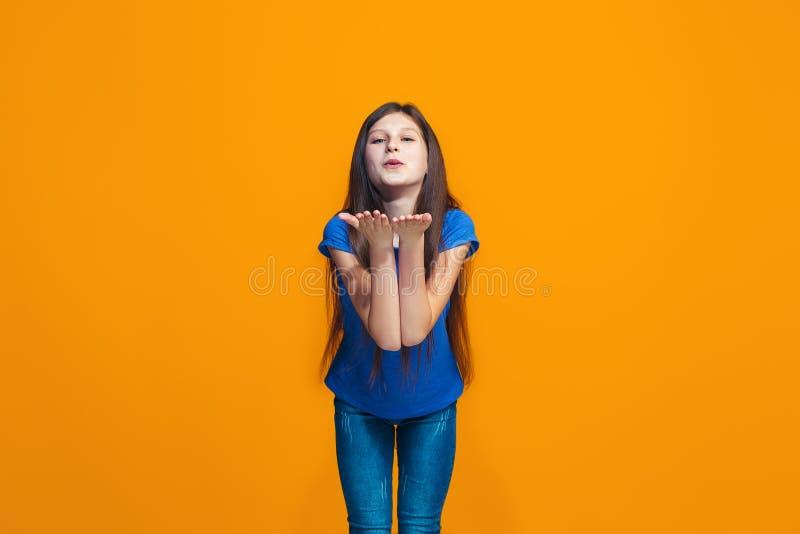 Το ευτυχές κορίτσι εφήβων που στέκεται και που χαμογελά στο πορτοκαλί κλίμα στοκ εικόνες με δικαίωμα ελεύθερης χρήσης