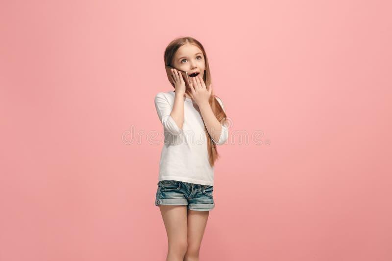 Το ευτυχές κορίτσι εφήβων που στέκεται και που χαμογελά στο ρόδινο κλίμα στοκ εικόνες