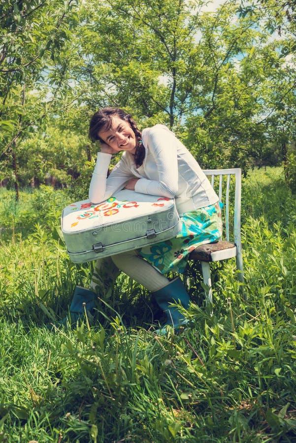 Το ευτυχές κορίτσι κάθεται με μια χρωματισμένη βαλίτσα στοκ φωτογραφία με δικαίωμα ελεύθερης χρήσης