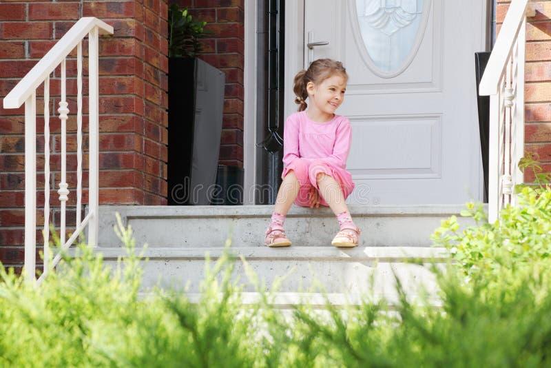 Το ευτυχές κορίτσι κάθεται στα σκαλοπάτια κοντά στην πόρτα, χαμογελά στοκ εικόνες με δικαίωμα ελεύθερης χρήσης