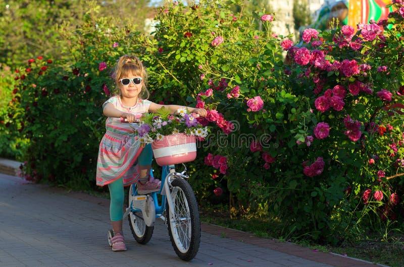 Το ευτυχές κορίτσι οδηγά ένα ποδήλατο με τα λουλούδια σε ένα καλάθι στοκ φωτογραφία με δικαίωμα ελεύθερης χρήσης