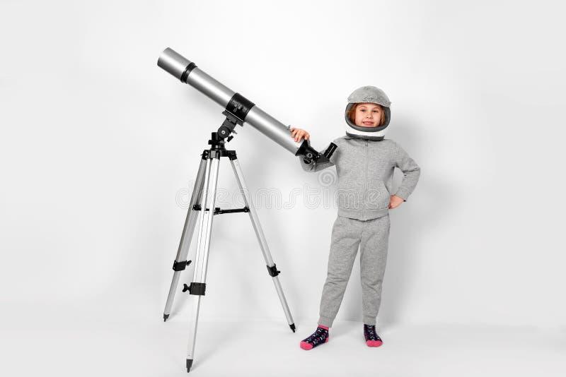 Το ευτυχές κορίτσι παιδιών έντυσε σε ένα κοστούμι αστροναυτών που στέκεται εκτός από το τηλεσκόπιο στοκ εικόνα με δικαίωμα ελεύθερης χρήσης