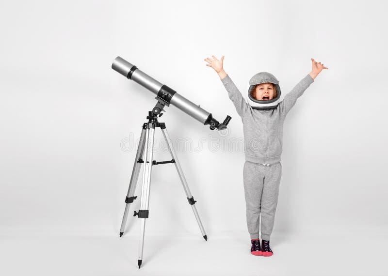 Το ευτυχές κορίτσι παιδιών έντυσε σε ένα κοστούμι αστροναυτών που στέκεται εκτός από το τηλεσκόπιο στοκ εικόνες
