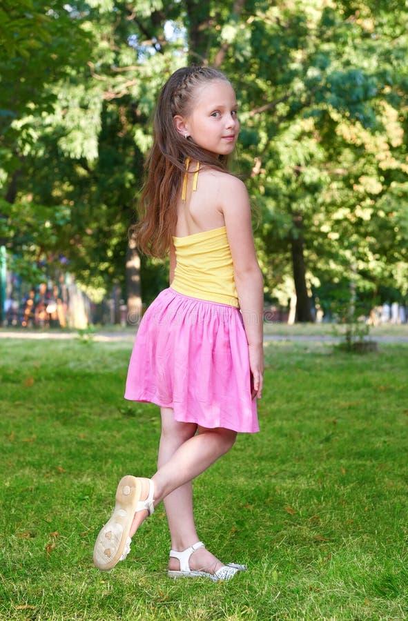 Το ευτυχές κορίτσι παιδιών έντυσε στην περιστασιακή τοποθέτηση υφασμάτων, έννοια παιδικής ηλικίας, θερινή περίοδο στο πάρκο πόλεω στοκ εικόνα με δικαίωμα ελεύθερης χρήσης