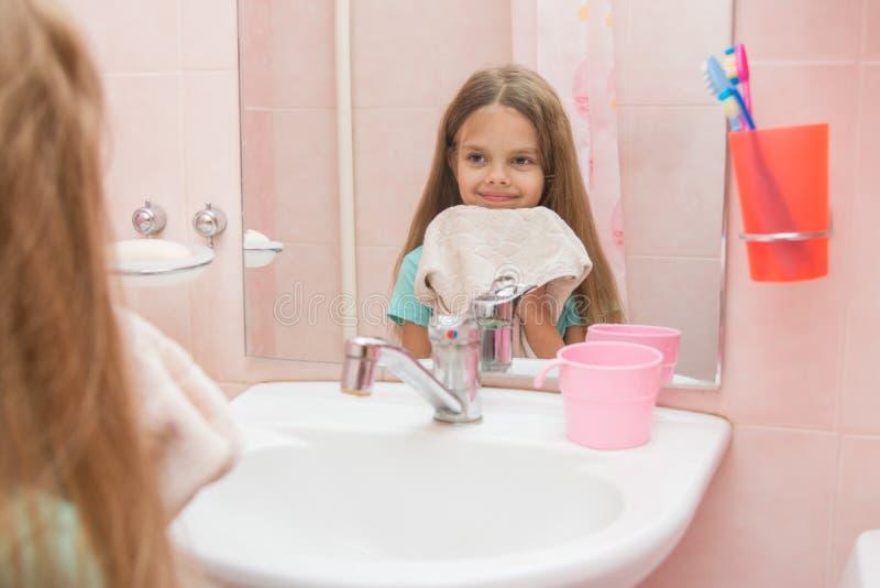 Το ευτυχές κορίτσι σκουπίζει την υγρή πετσέτα προσώπου της στο λουτρό στοκ εικόνες