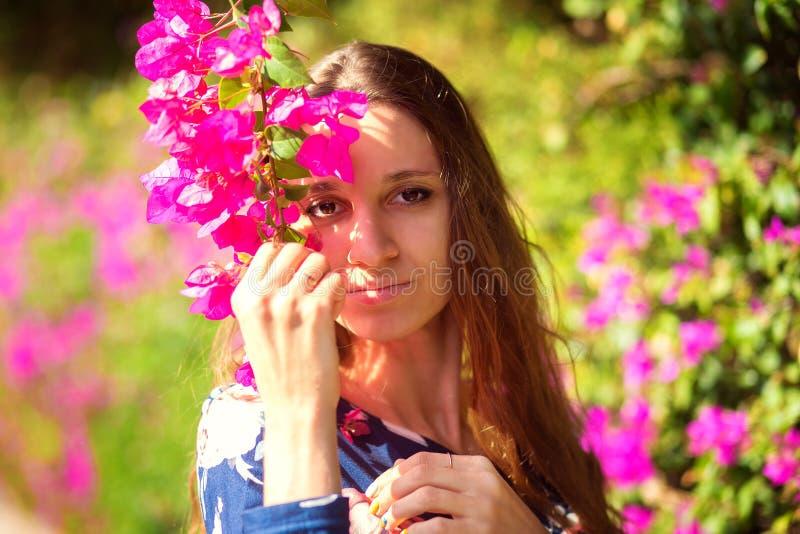 Το ευτυχές κορίτσι στον ανθίζοντας θάμνο με τα ρόδινα χρώματα στην Τουρκία Το κορίτσι κρατά έναν κλάδο της πορφυρής ανθίζοντας αζ στοκ φωτογραφία με δικαίωμα ελεύθερης χρήσης