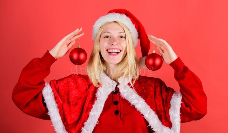 Το ευτυχές κοστούμι santa ένδυσης κοριτσιών γιορτάζει το ντεκόρ σφαιρών λαβής Χριστουγέννων το αντίγραφο έννοιας Χριστουγέννων χω στοκ εικόνα με δικαίωμα ελεύθερης χρήσης