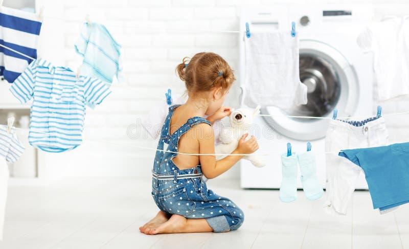 Το ευτυχές μικρό κορίτσι διασκέδασης παιδιών για να πλύνει τα ενδύματα και teddy αντέχει στο λ στοκ εικόνες