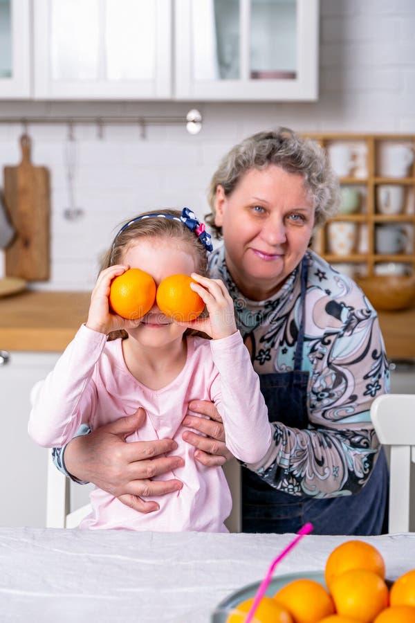 Το ευτυχές μικρό κορίτσι και η γιαγιά της έχουν το πρόγευμα μαζί σε μια άσπρη κουζίνα Έχουν τη διασκέδαση και παίζουν με τα φρούτ στοκ εικόνες