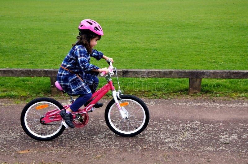 Το ευτυχές μικρό κορίτσι μαθαίνει πώς να οδηγήσει ένα ποδήλατο στοκ φωτογραφίες
