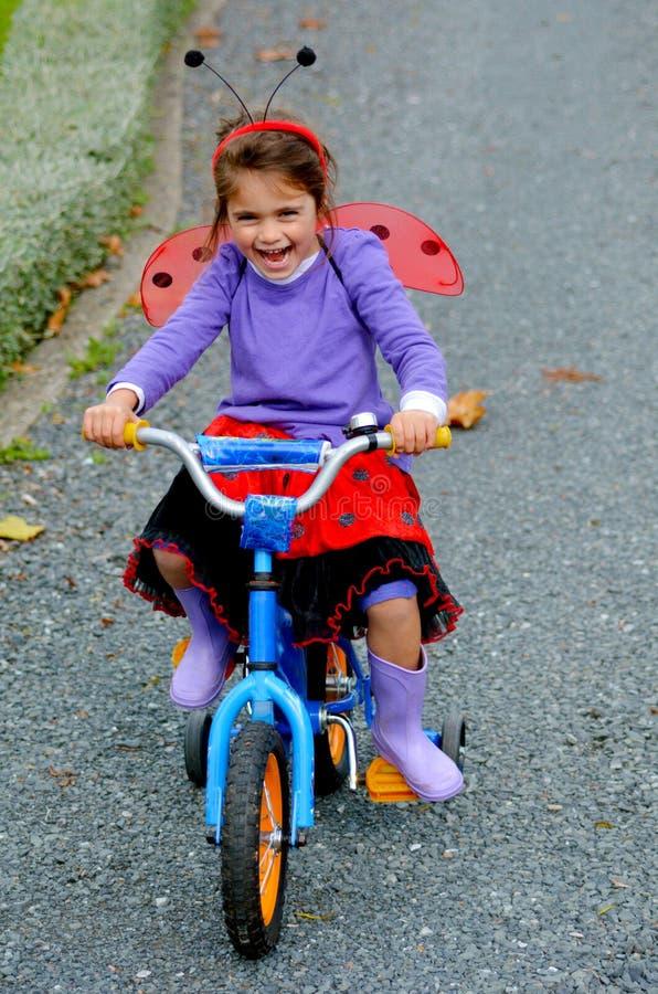 Το ευτυχές μικρό κορίτσι οδηγά ένα ποδήλατο στοκ εικόνες με δικαίωμα ελεύθερης χρήσης