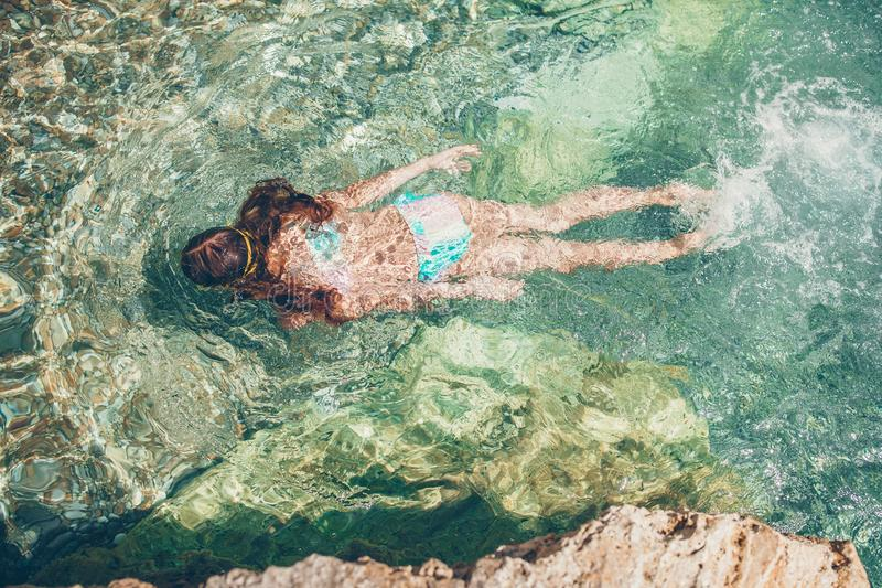 Το ευτυχές μικρό κορίτσι που κολυμπά με αναπνευτήρα στη μάσκα βουτά υποβρύχιος με τα τροπικά ψάρια στοκ φωτογραφία