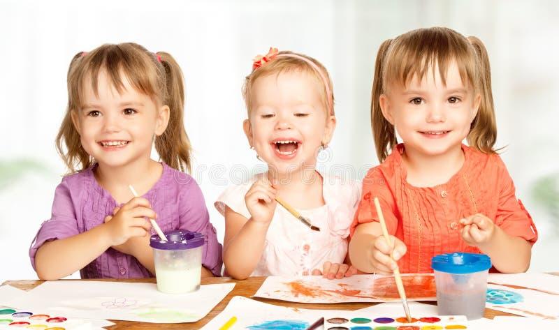 Το ευτυχές μικρό κορίτσι στον παιδικό σταθμό σύρει τα χρώματα στοκ εικόνα με δικαίωμα ελεύθερης χρήσης