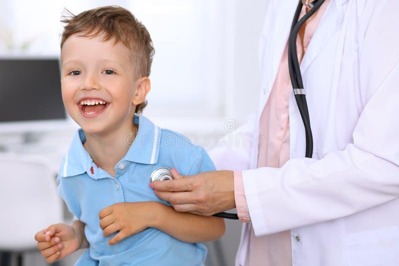 Το ευτυχές μικρό παιδί που έχει τη διασκέδαση ενώ είναι εξετάζει από το γιατρό από το στηθοσκόπιο Υγειονομική περίθαλψη, ασφάλεια στοκ εικόνα