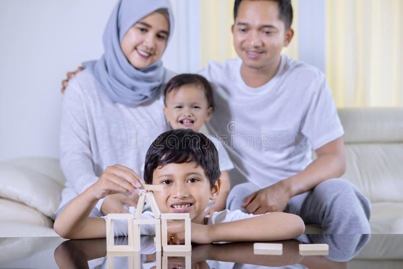 Το ευτυχές μικρό παιδί χτίζει ένα σπίτι με την οικογένειά του στοκ φωτογραφία με δικαίωμα ελεύθερης χρήσης
