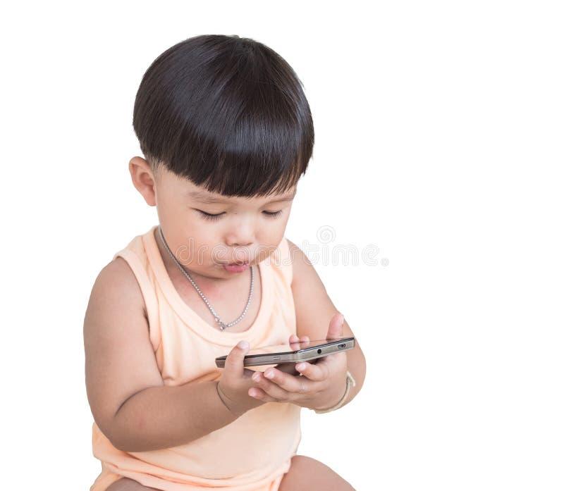 Το ευτυχές μικρό παιδί κάνει το πρόσωπο αντίδρασης ελέγχοντας το smartphone με το ψαλίδισμα της πορείας στοκ φωτογραφίες με δικαίωμα ελεύθερης χρήσης
