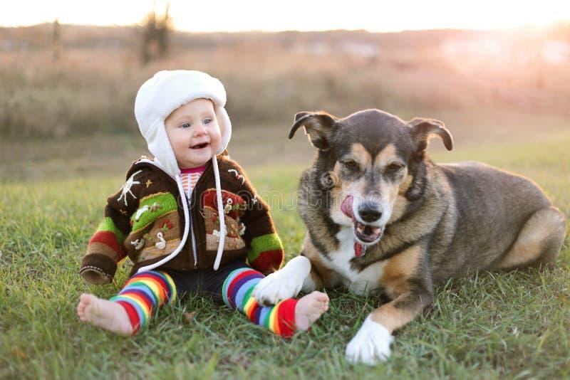 Το ευτυχές μωρό συσσώρευσε επάνω έξω το χειμώνα με το σκυλί της Pet στοκ φωτογραφία με δικαίωμα ελεύθερης χρήσης
